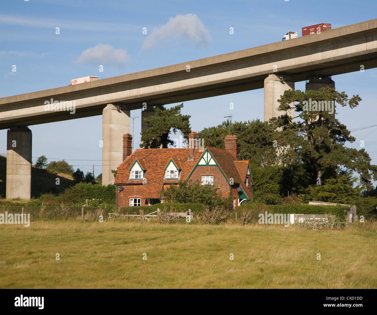Raised A14 trunk road on Orwell Bridge above farmhouse Wherstead, Suffolk, England - Stock Image