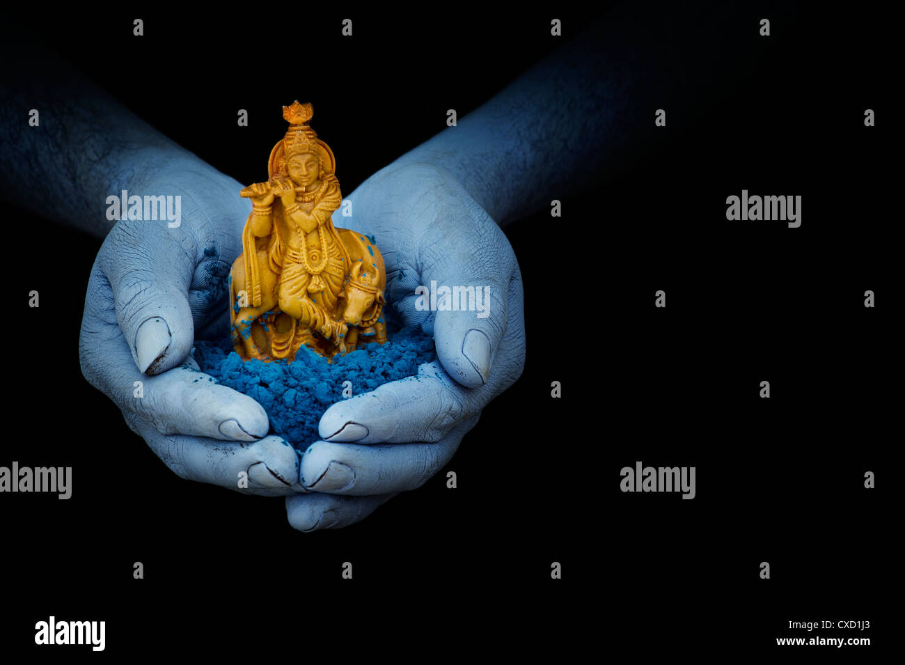 blue indian mans hands holding lord krishna statue and blue powder CXD1J3