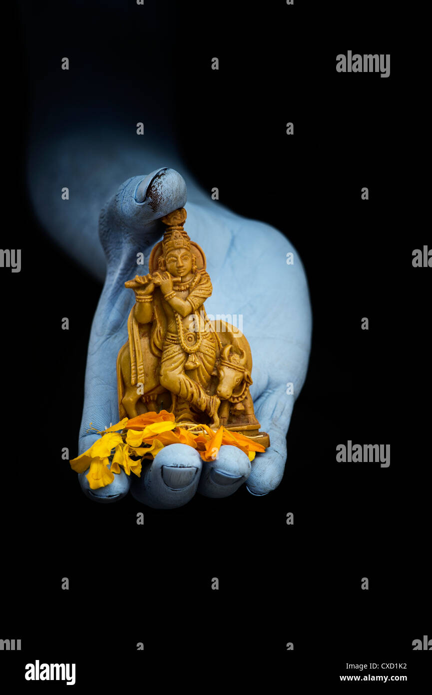 blue indian mans hand holding lord krishna statue and flower petals CXD1K2