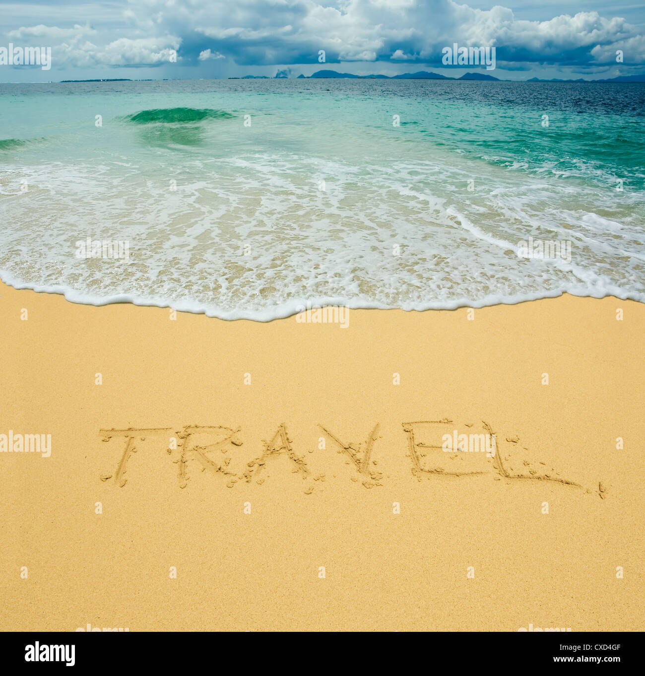 travel written in a sandy tropical beach - Stock Image