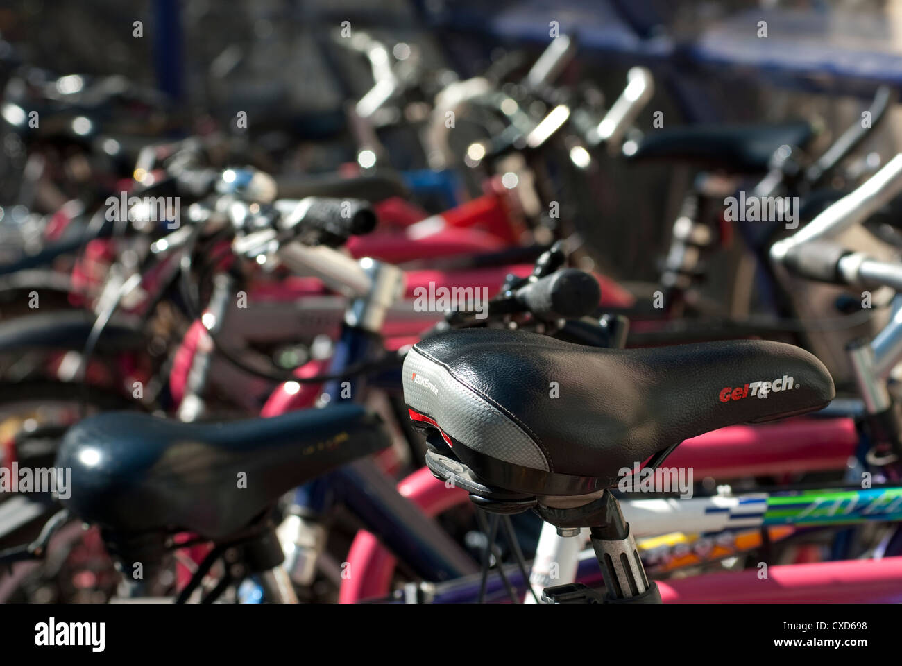Bicycles parked securely undercover in a parking area outside a railway station in England. - Stock Image
