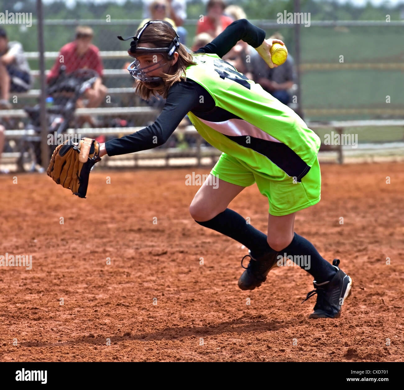 A young pitcher with ball in hand racing to make an out in a softball game. - Stock Image