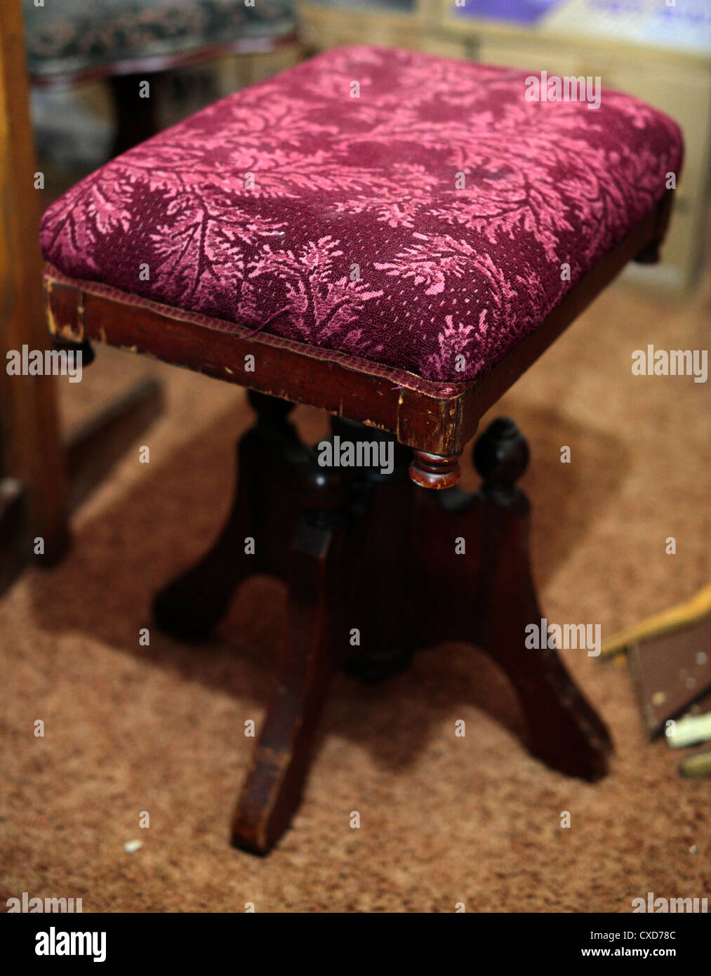 A square fabric-covered organ stool. - Stock Image