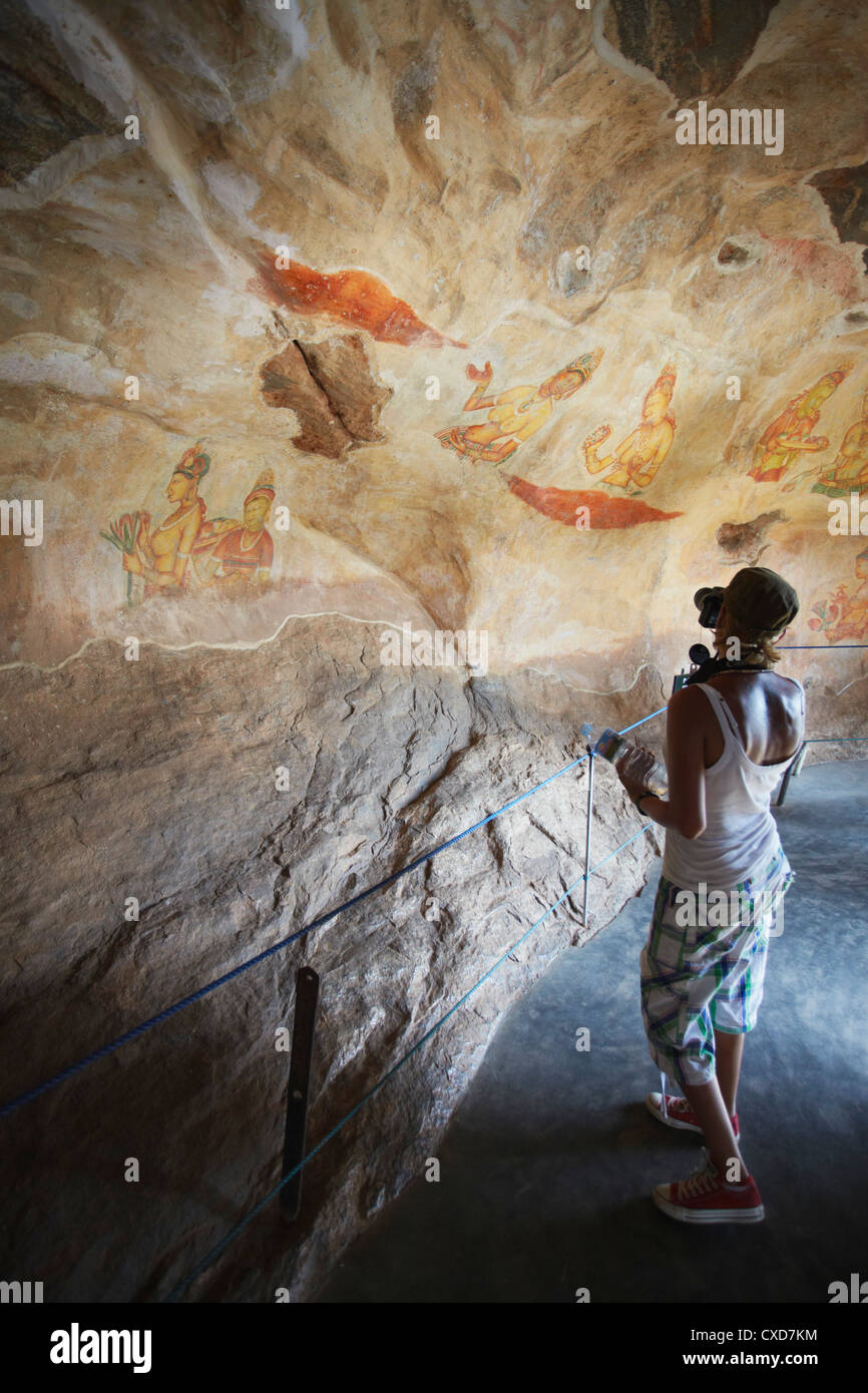 Tourist taking photos of ancient frescoes, Sigiriya, UNESCO World Heritage Site, North Central Province, Sri Lanka, - Stock Image
