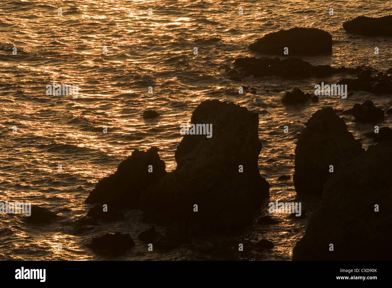 jagged rocks rocks hidden sea waves coast coastline ragged dusk dark - Stock Image