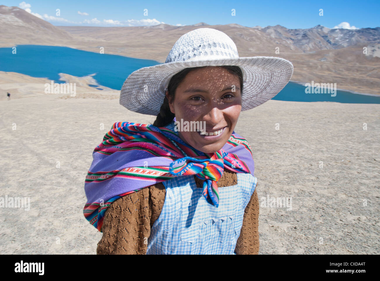 Aymara woman in the Cordillera Real with the Lake Tuni in the background - Stock Image