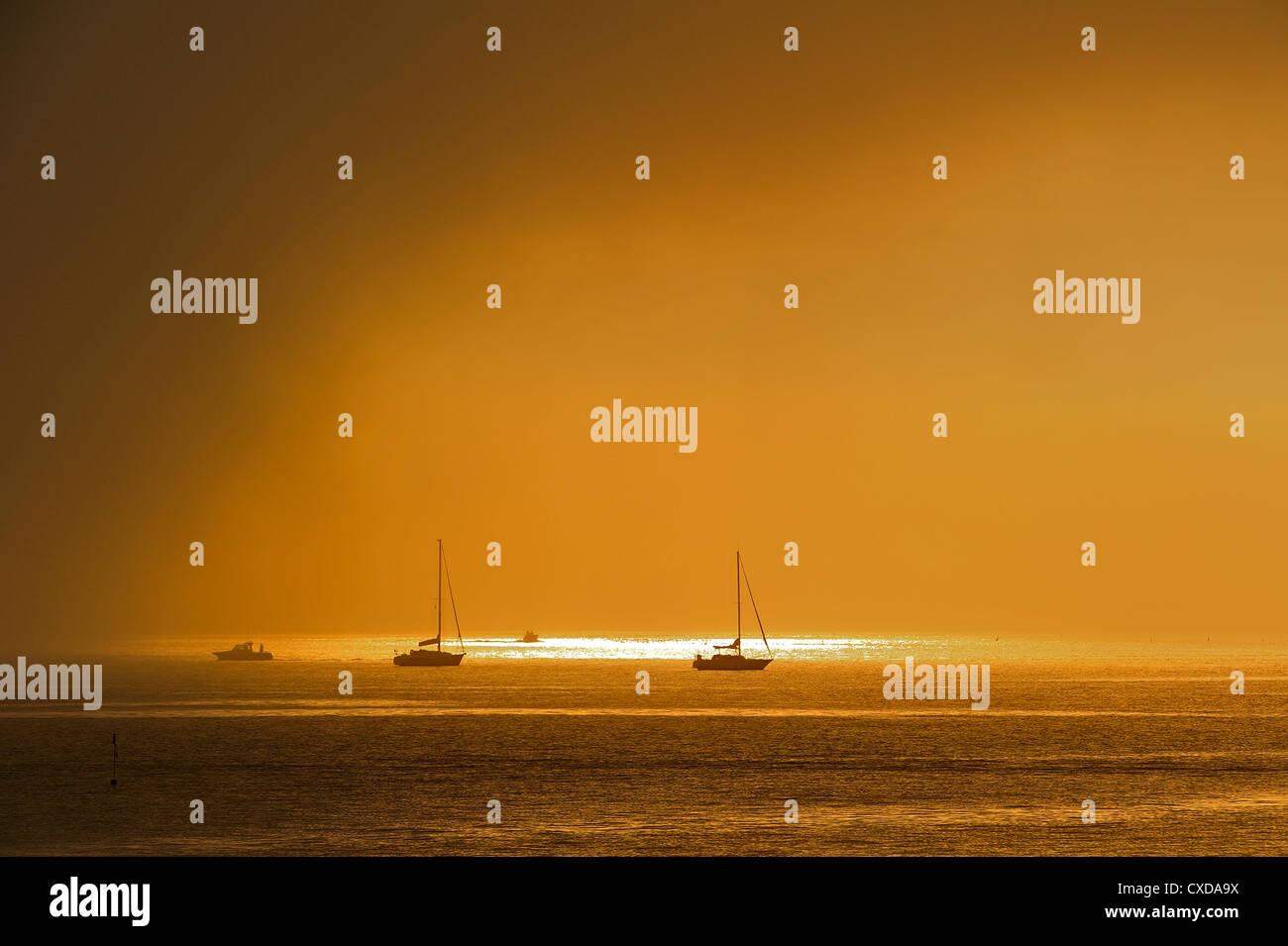 Rain cloud passing over sailing boats at sunset at Saint-Denis-d'Oléron on the island Ile d'Oléron, - Stock Image