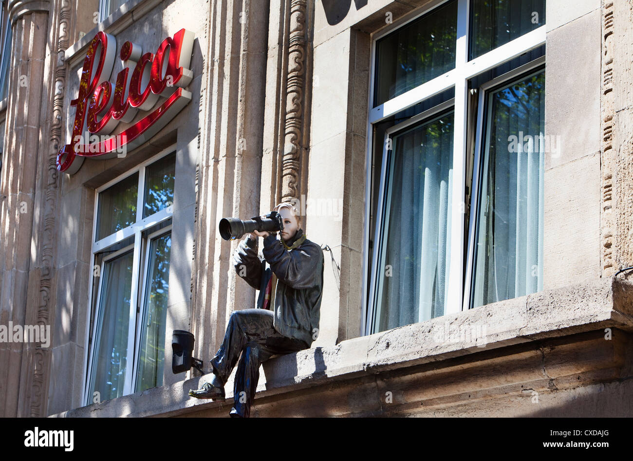 A figure as a photographer with a Camera and a big lens - Stock Image