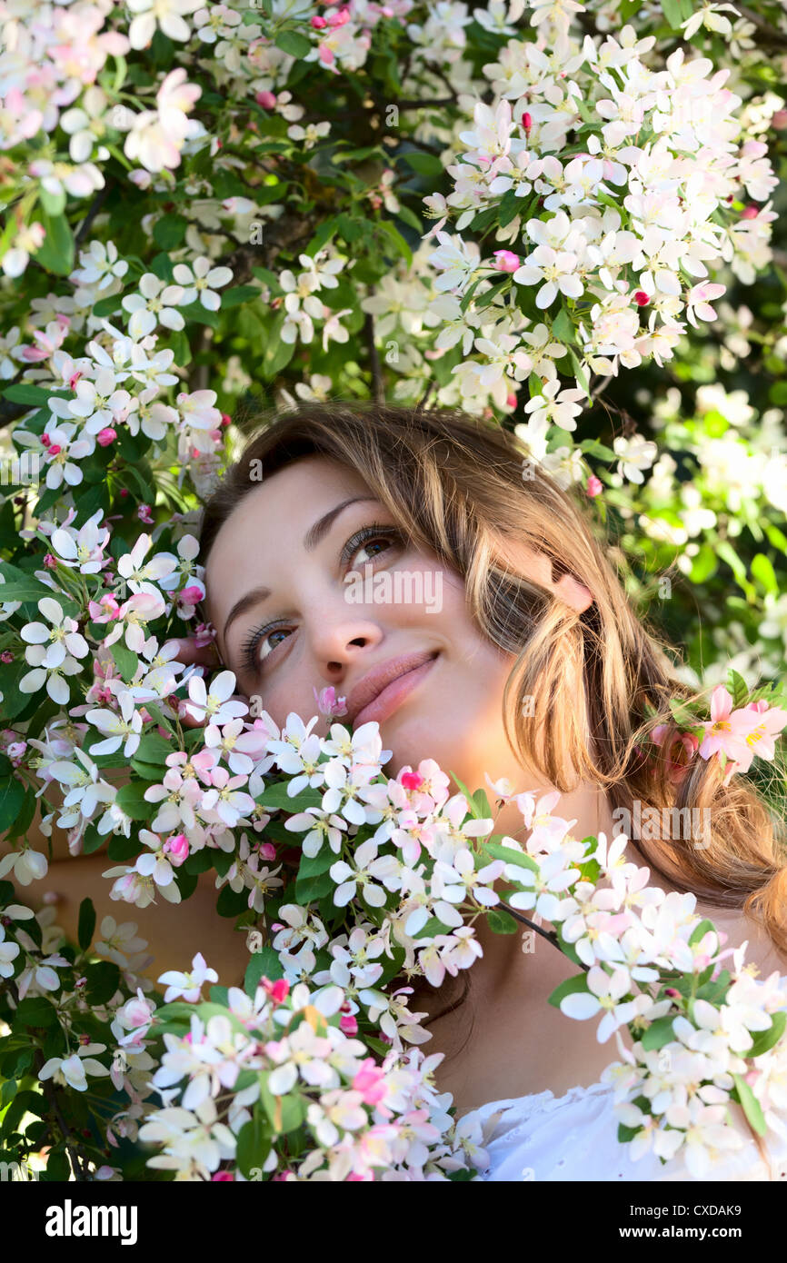 Pretty woman among a spring blossom - Stock Image