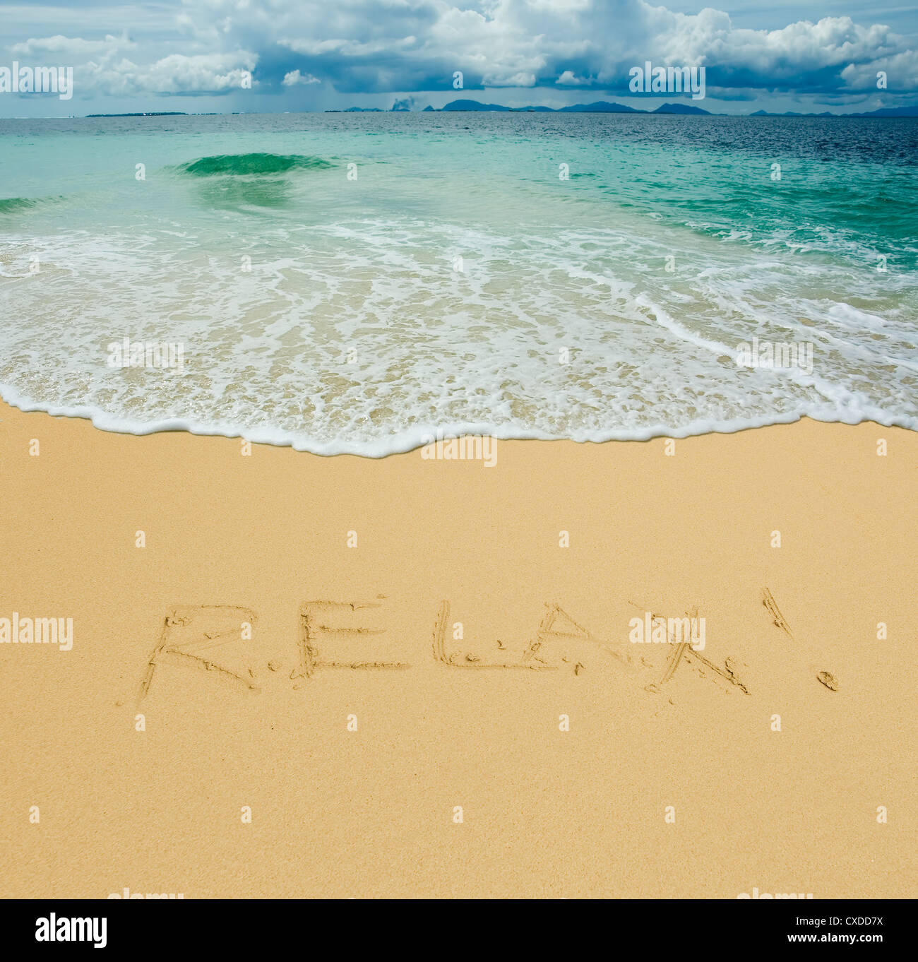 relax written in a sandy tropical beach - Stock Image