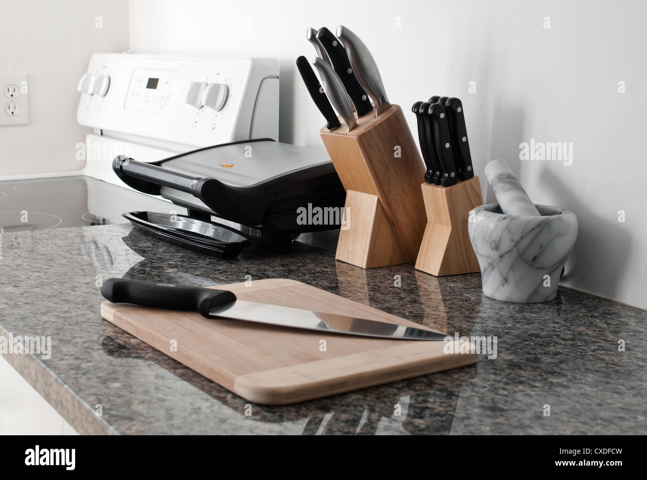 Gray granite counter with knives, mortar and pestle, panini grill and oven in a white kitchen - Stock Image