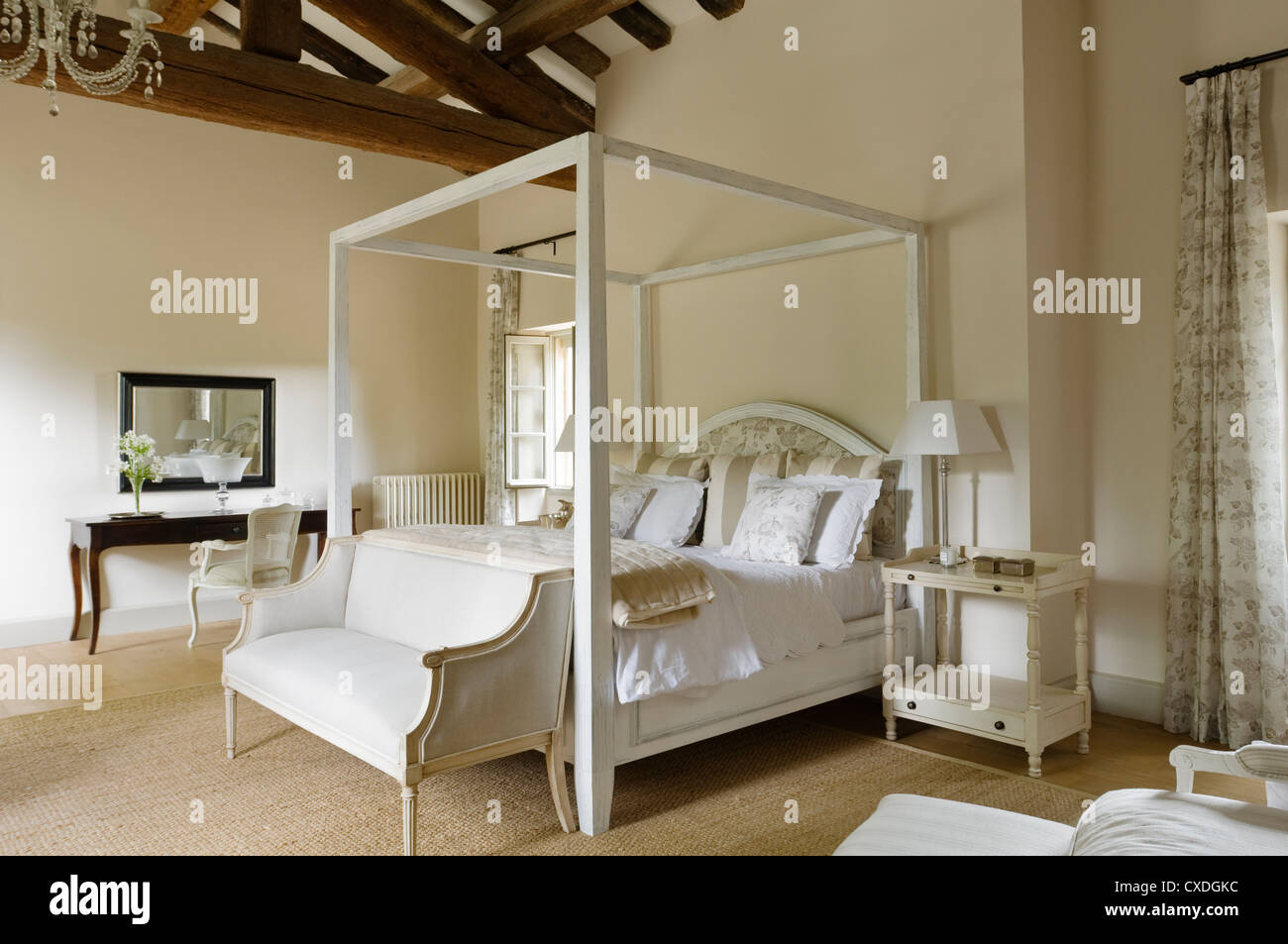 White four poster bed below high beamed ceiling of Provence country house - Stock Image