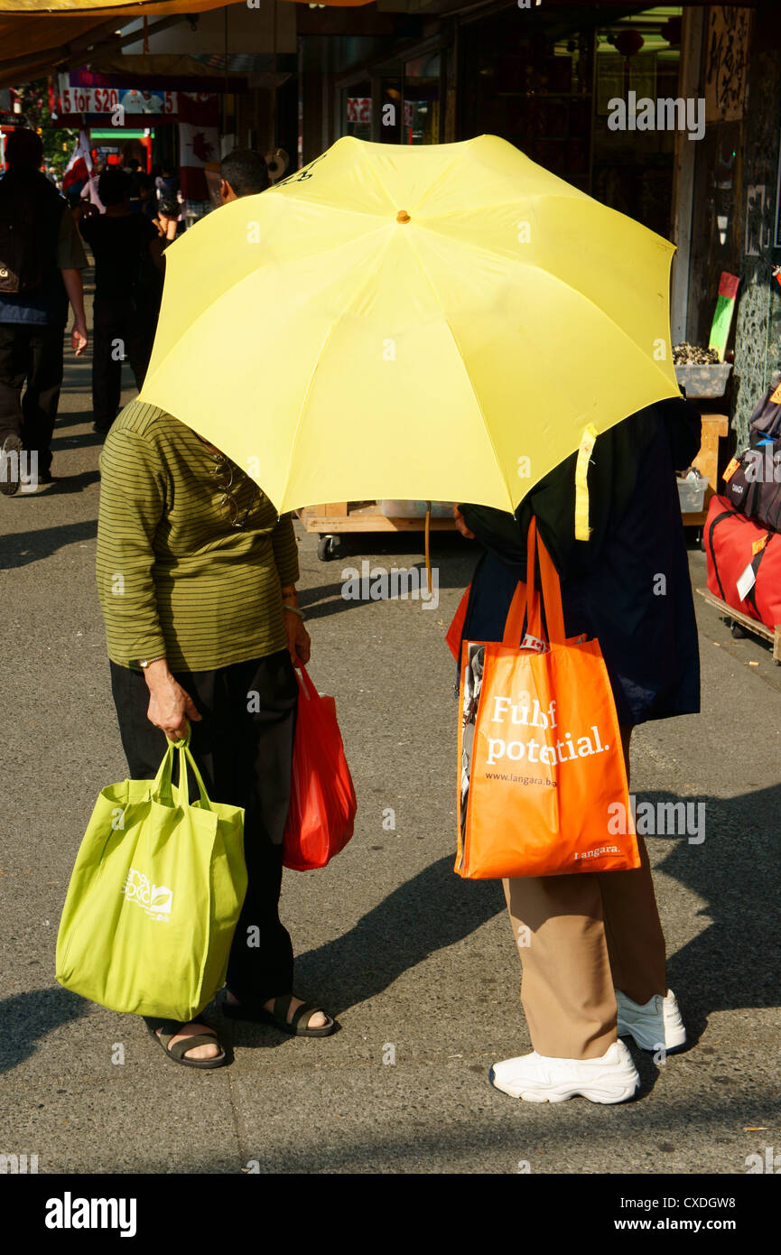Two Chinese women chatting under a yellow parasol, Chinatown, Vancouver, British Columbia, Canada - Stock Image