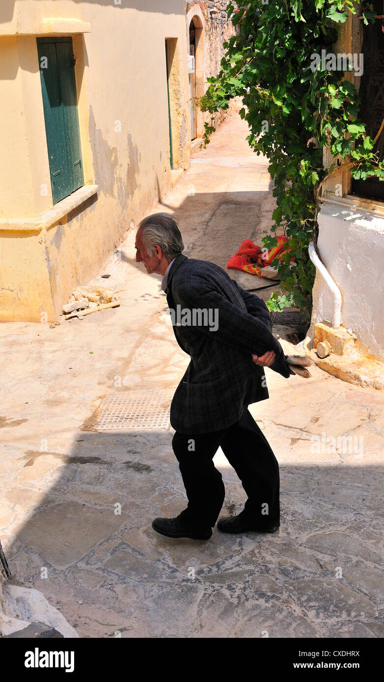 Man with stooped back(reported to be the church bell ringer) walks to the Church through the  lanes of hilltop village - Stock Image