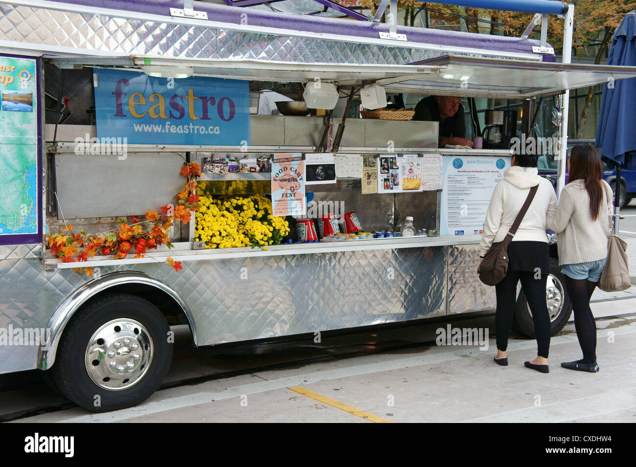 Two young women placing orders at a gourmet street food cart
