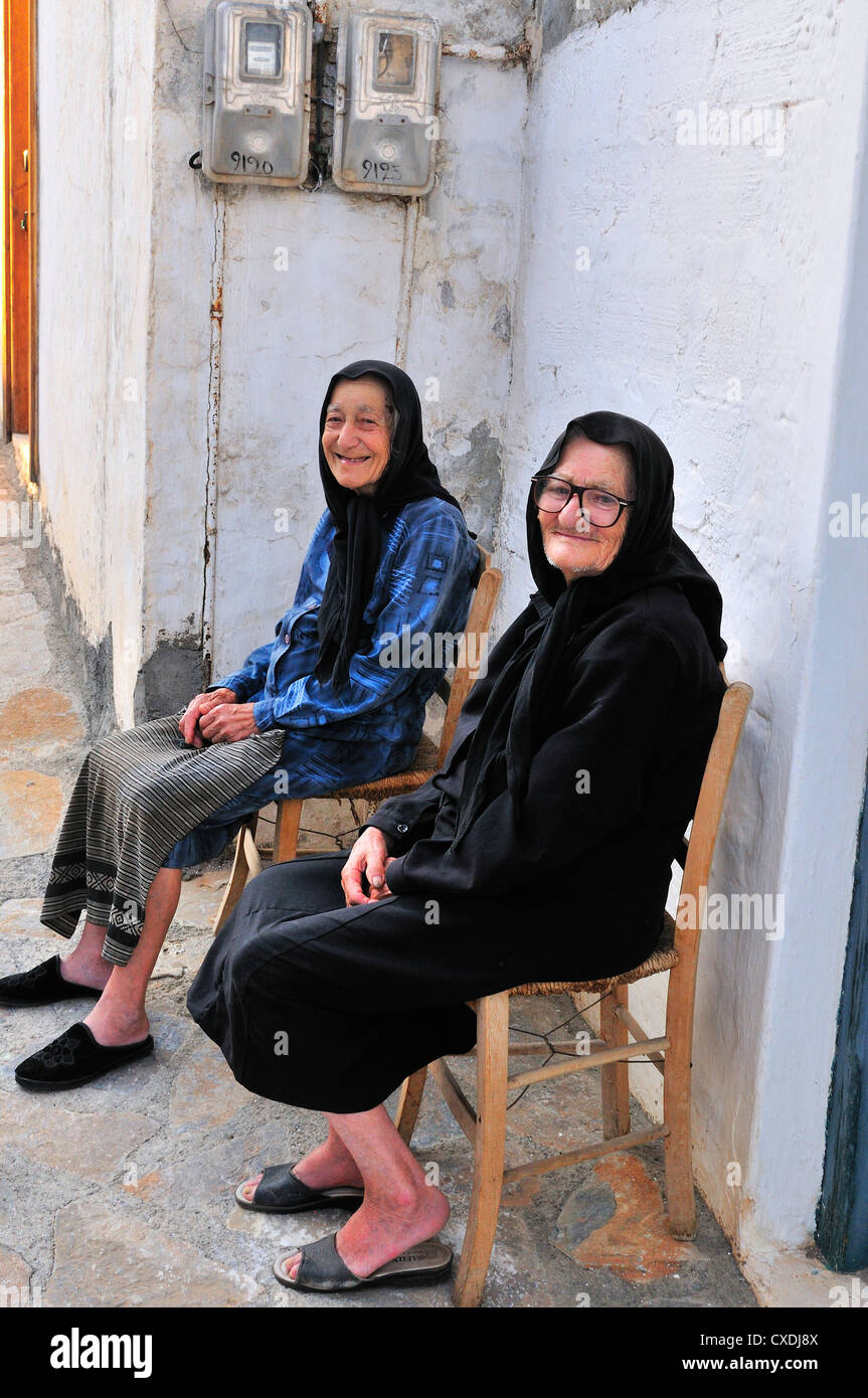 two old ladies sit outside their homes talking in a shaded alley, away from the   intense  Junes heats in hill top - Stock Image