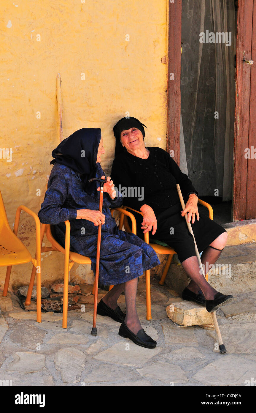 Two old ladies sit  outside their homes gossiping together in a shaded alleyway in  the  hilltop village  Pano Elounda, - Stock Image