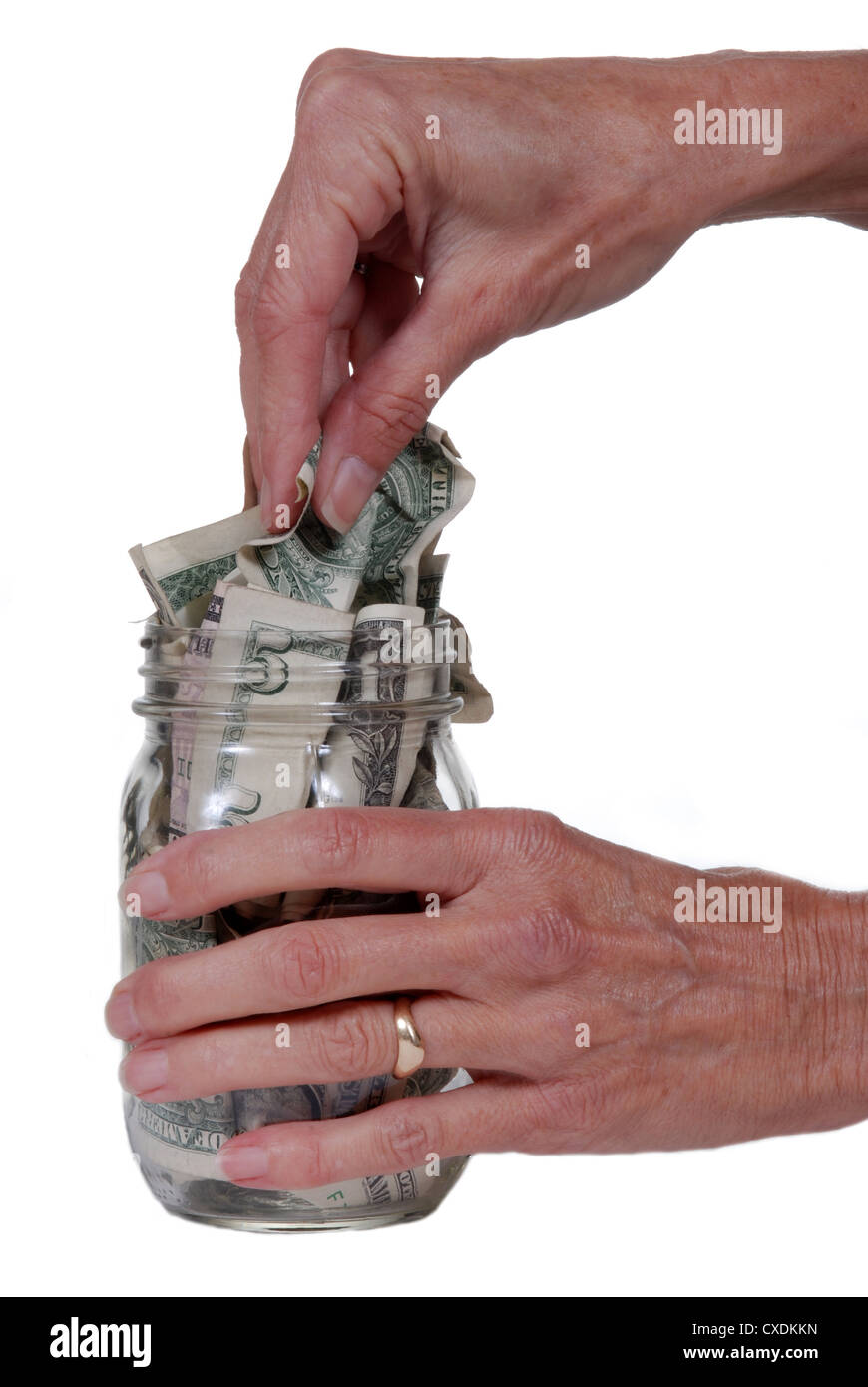 Female hand taking dollar bills out of glass jar. Isolated on white. Stock Photo