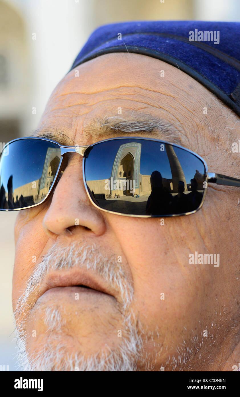 The Kalon mosque in Bukhara reflected on an Uzbek's man sunglasses. Stock Photo