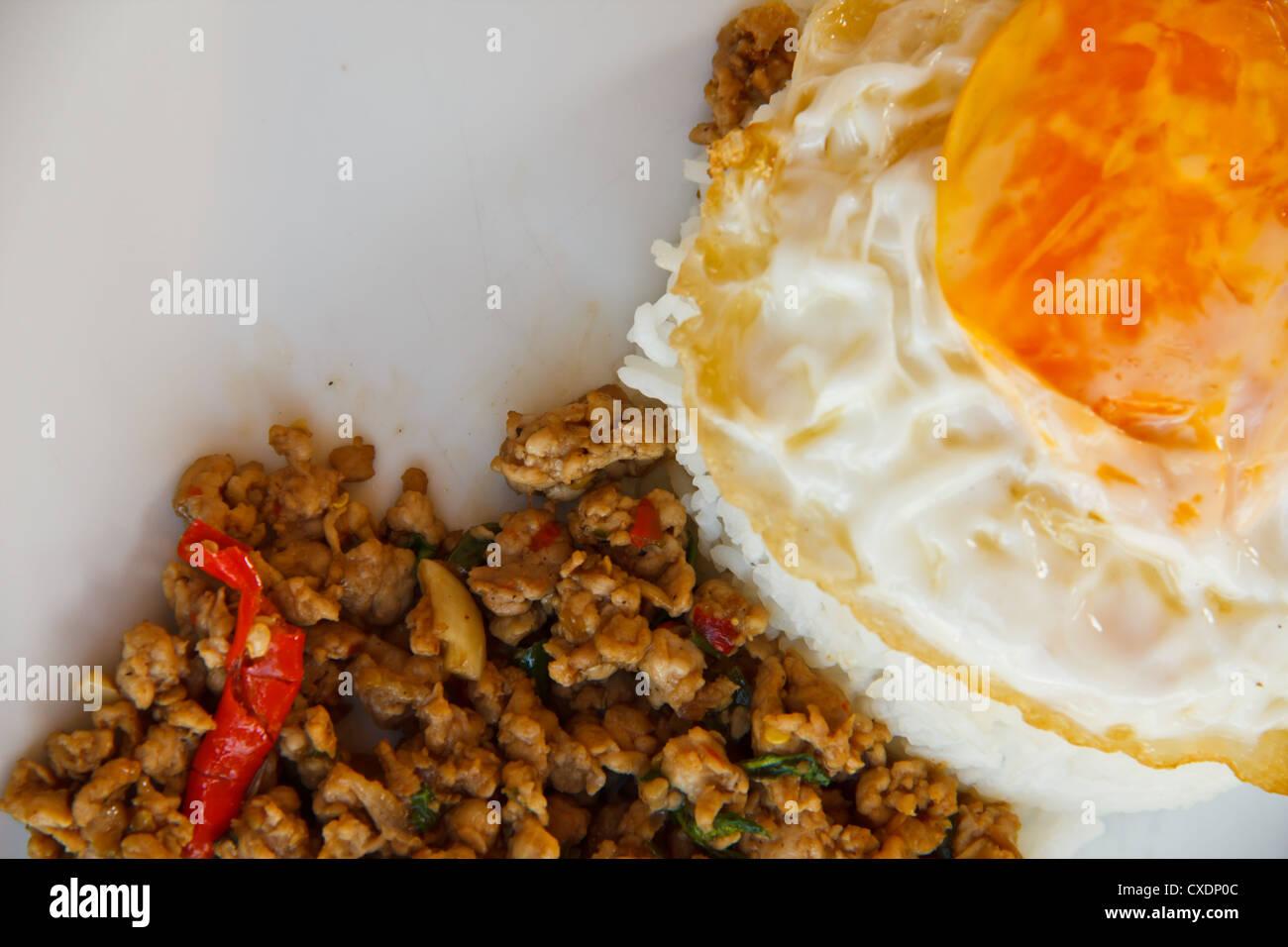 Pad Krapow Moo, spicy stir-fried pork with fried egg and Thai holy basil, Thai cuisine - Stock Image