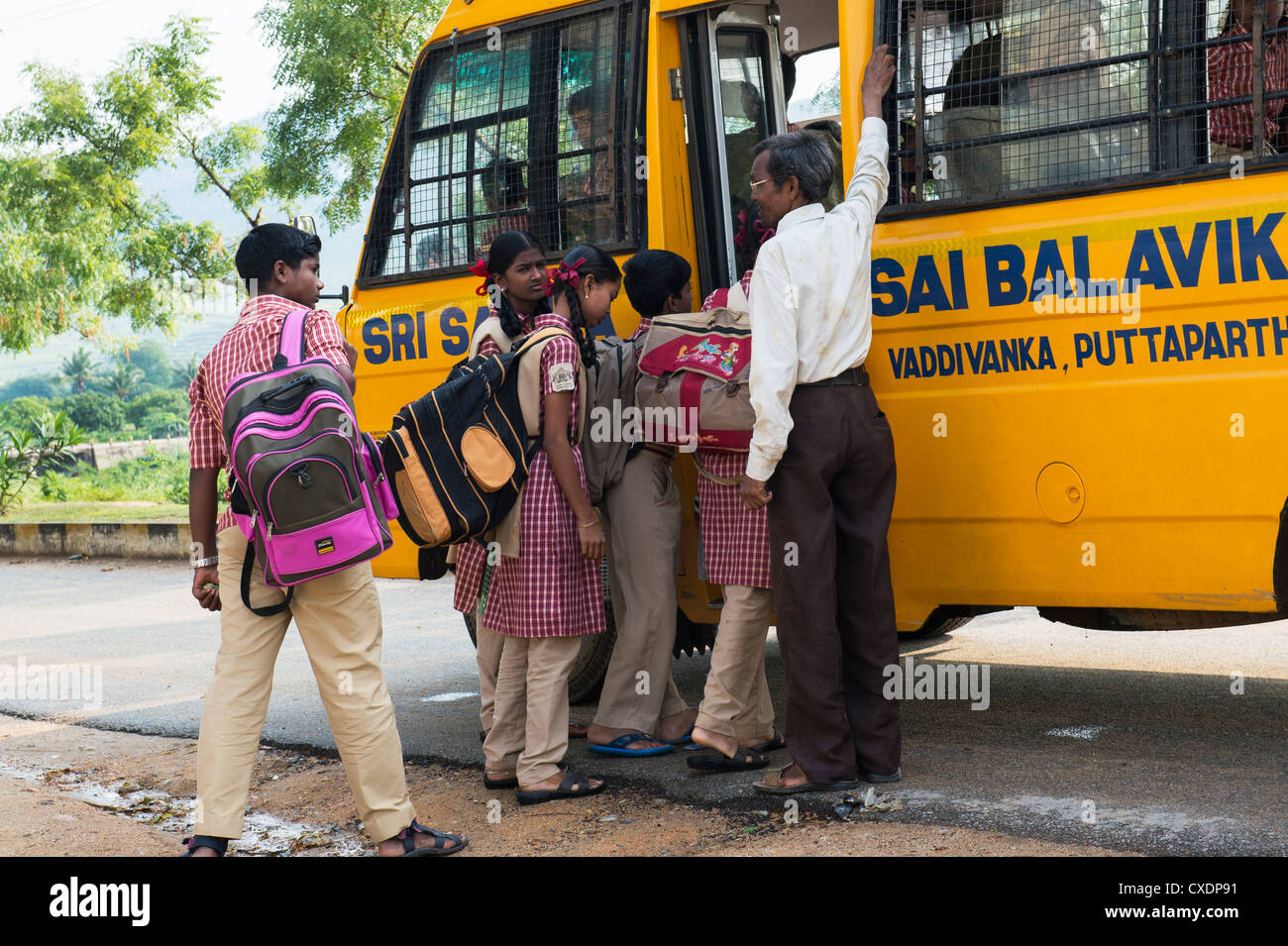 Indian School Children Getting On A School Bus Being Supervised By