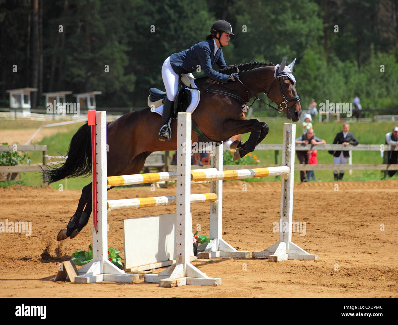 Young girl jumping with sorrel horse - Stock Image
