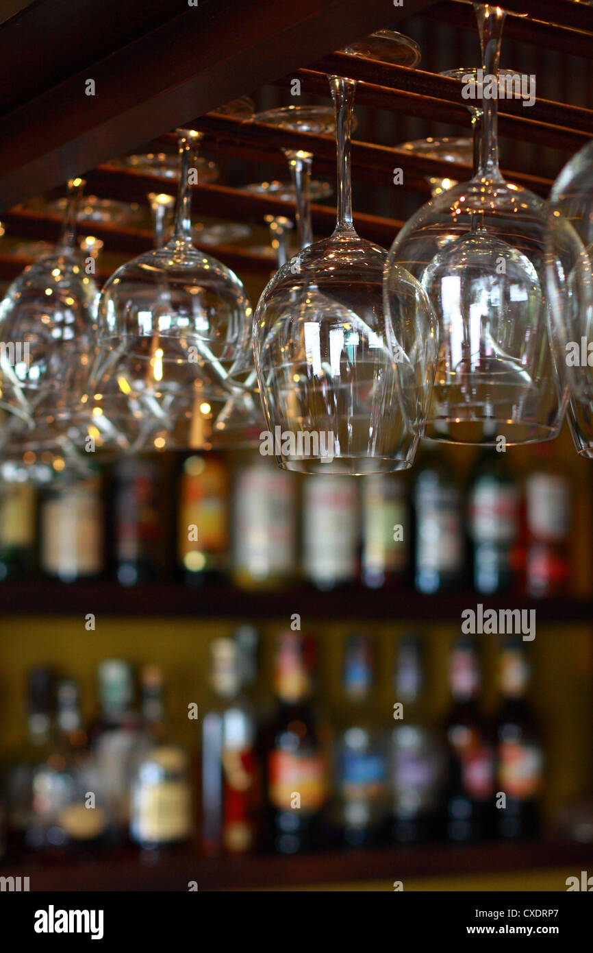 Empty glasses for wine above a bar rack - Stock Image