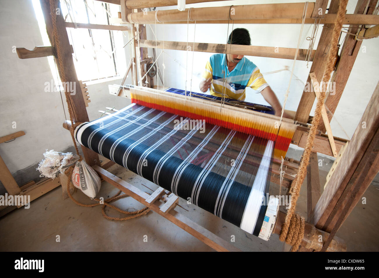 Man weaving coloured silk sari on domestic loom, rural Orissa, India, Asia - Stock Image