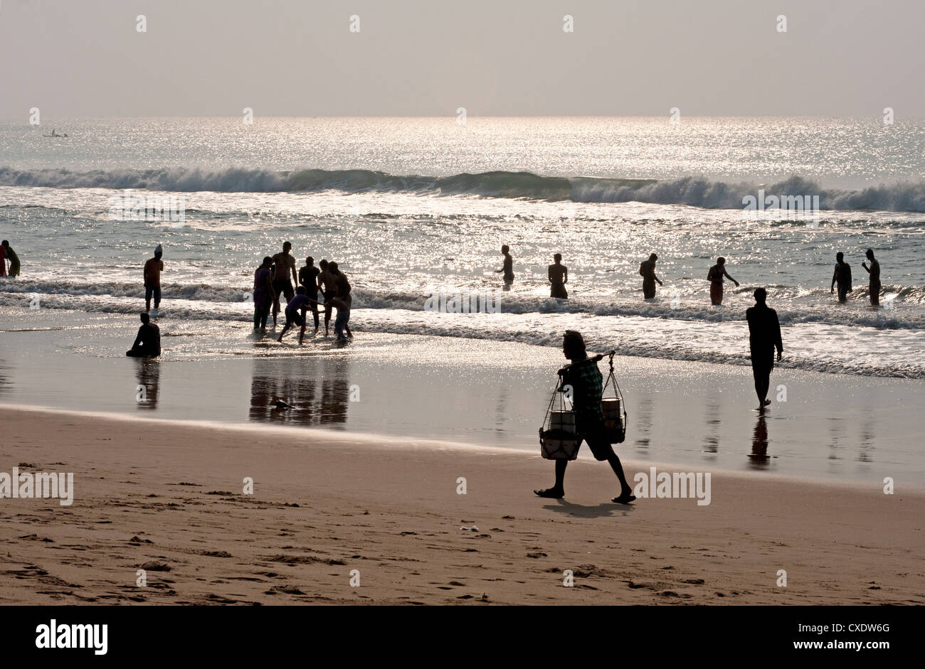 Puri beach on the Bay of Bengaln families relaxing and paddling, beach vendor walking by in the late afternoon, - Stock Image