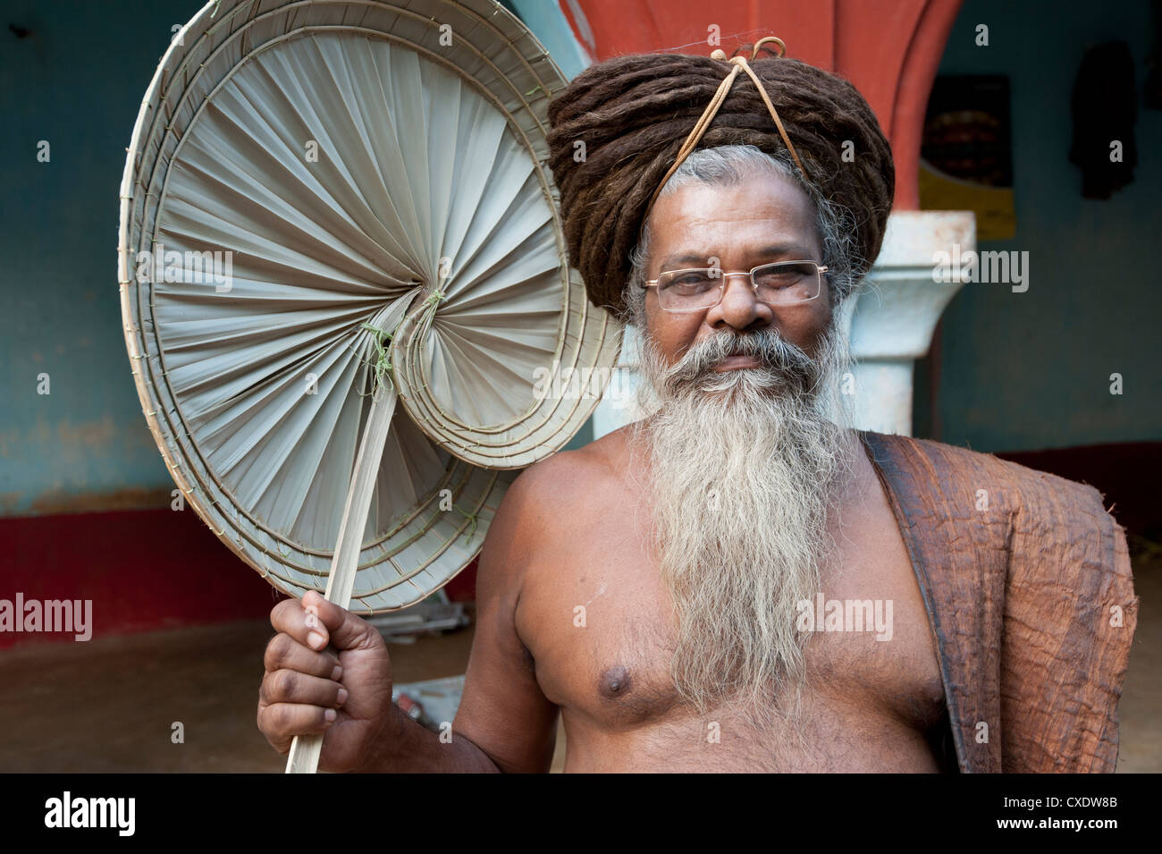 Joranda monk wearing tree bark cloth, holding palm leaf fan, with uncut hair piled up on top of his head, Joranda, - Stock Image