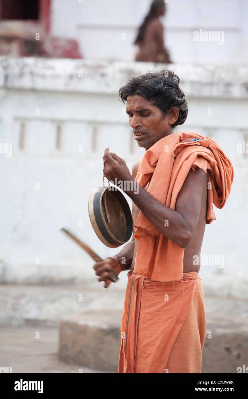 Joranda monk at dusk, wearing orange cloth, sounding a cymbal as preparation for ritual evening prayer, Joranda, - Stock Image