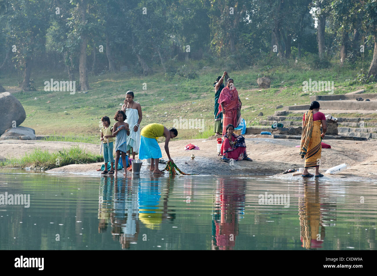 Women washing clothes on the ghats of the  River Mahanadi, reflected in the water, Orissa, India, Asia - Stock Image