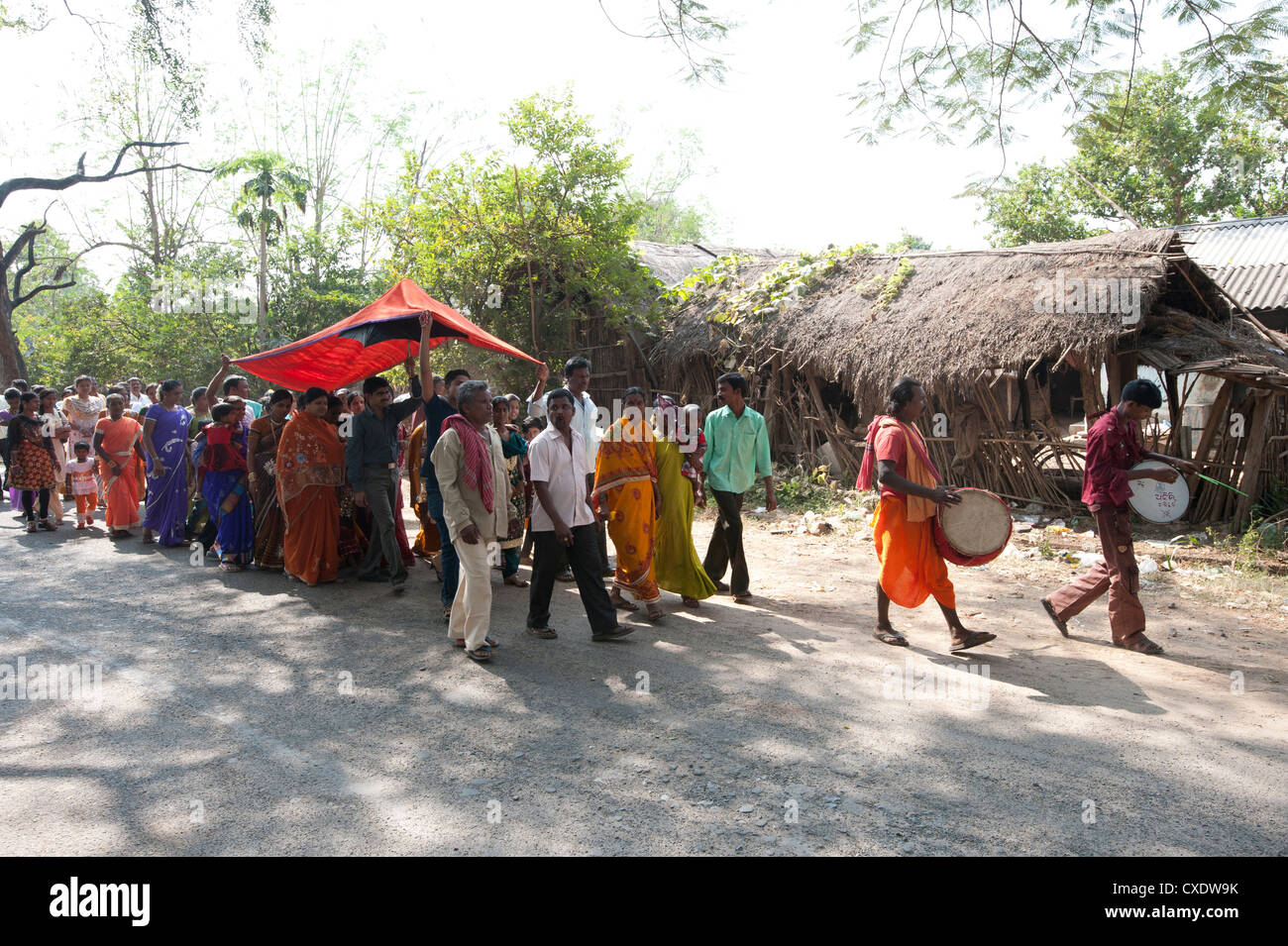 Drummers leading village bride under red canopy to her marriage ceremony in a procession with family and villagers, - Stock Image