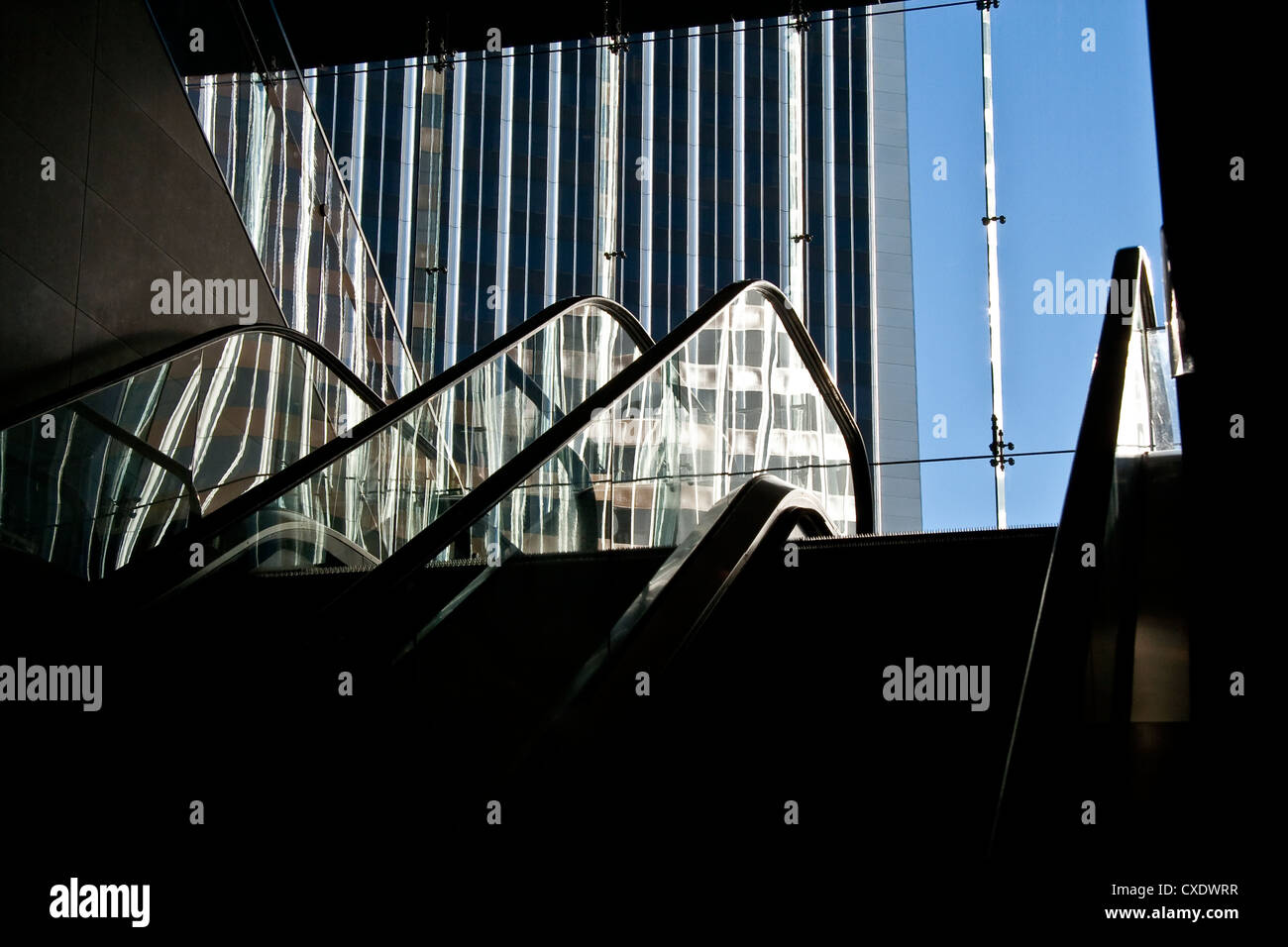 Escalator with outside view of blue sky and office building in Century City - Stock Image
