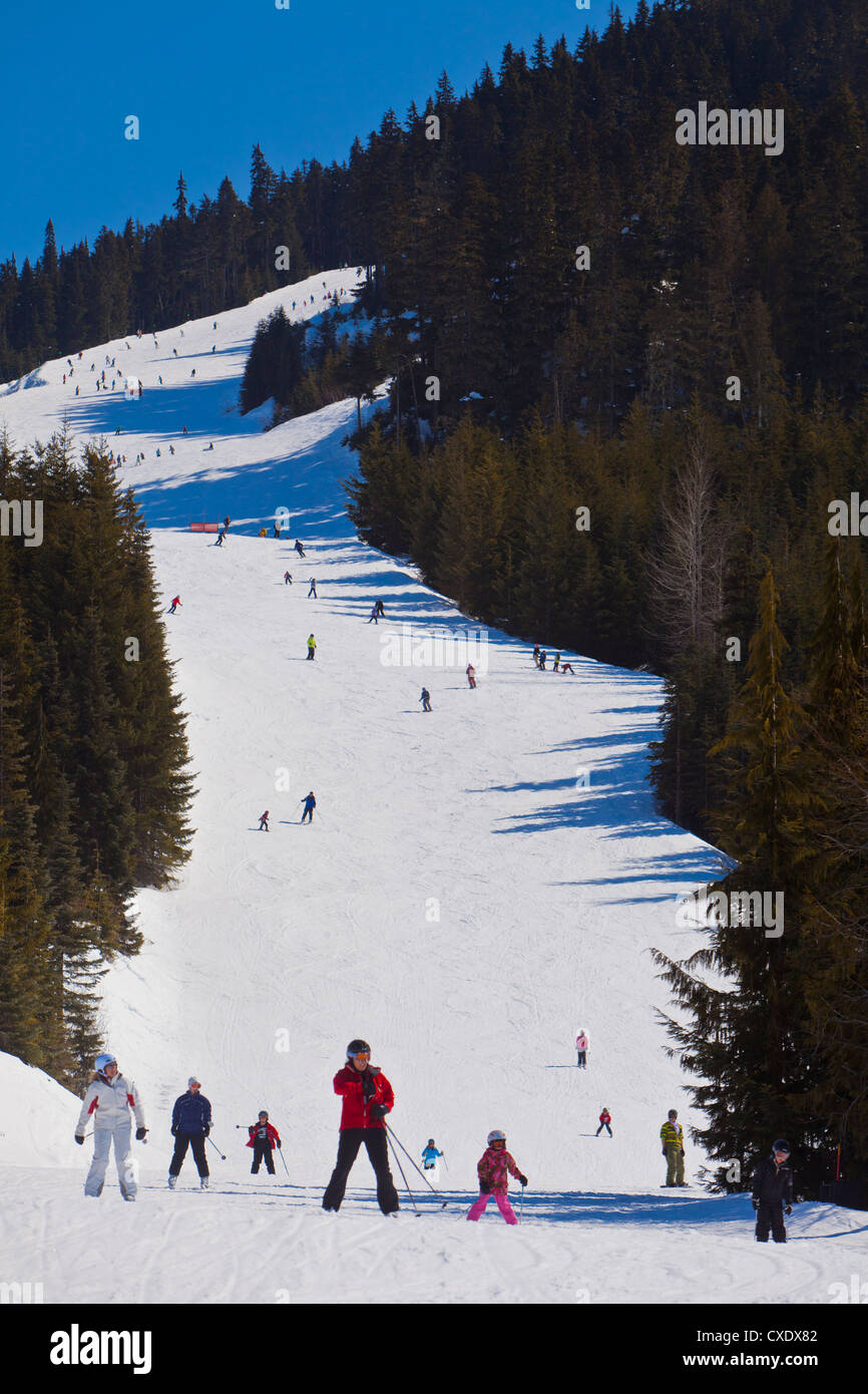Skiers and snowboarders going downhill on a run, Whistler Blackcomb Ski Resort, Whistler, British Columbia, Canada - Stock Image