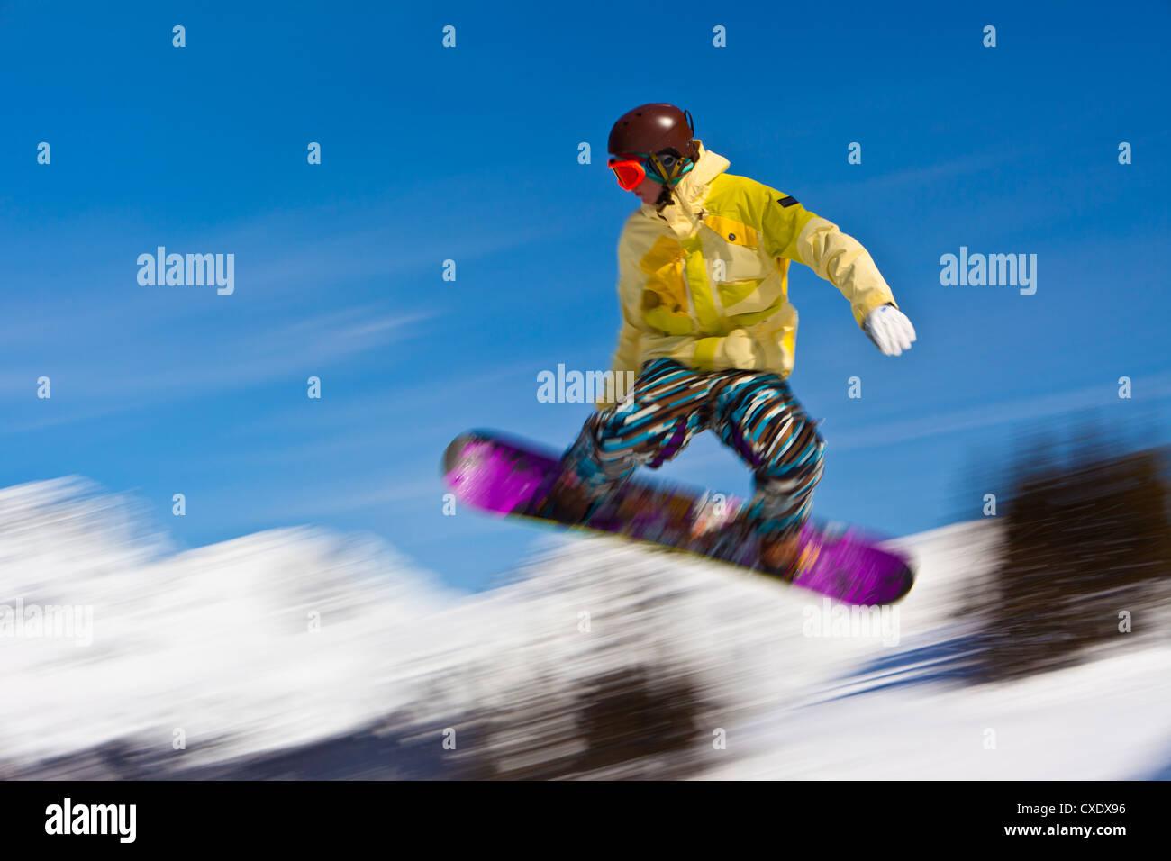 Snowboarder flying off a ramp, Whistler Mountain, Whistler Blackcomb Ski Resort, Whistler, British Columbia, Canada - Stock Image