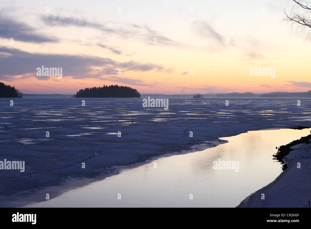Sunset over the mainly frozen surface of Lake Pyhajarvi, the ice surrounds islands, at Tampere, Pirkanmaa, Finland, - Stock Image