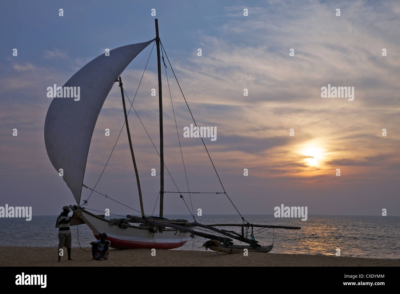 Fisherman and Oruvas (traditional outrigger dug-out canoe), Negombo beach, Western Province, Sri Lanka, Asia Stock Photo