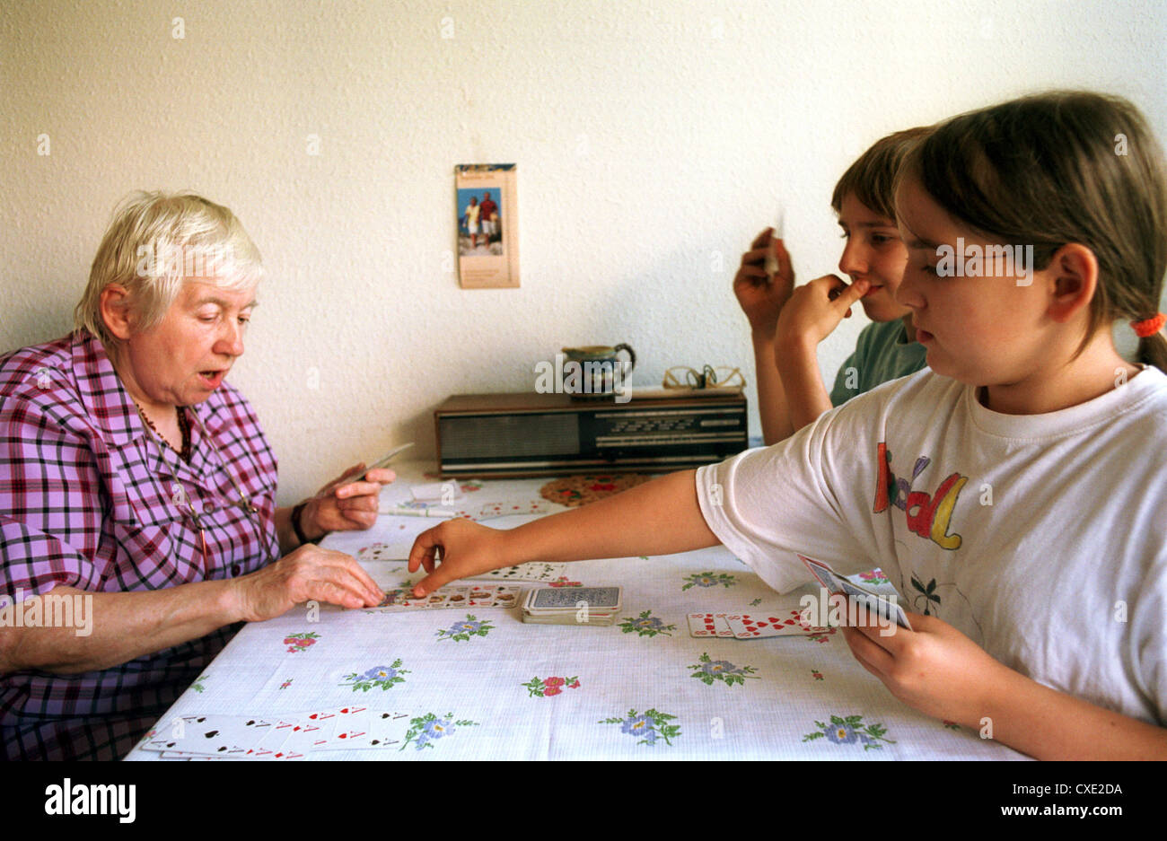 Berlin, a grandmother and granddaughter playing with grandchildren cards at the kitchen table Stock Photo