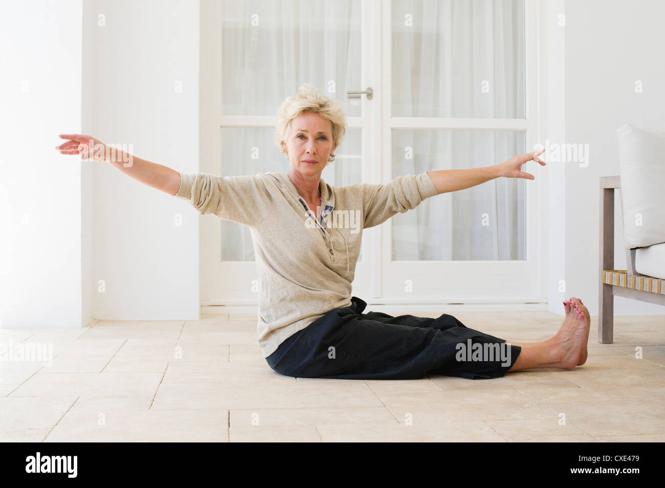 Mature woman practicing yoga on floor - Stock Image