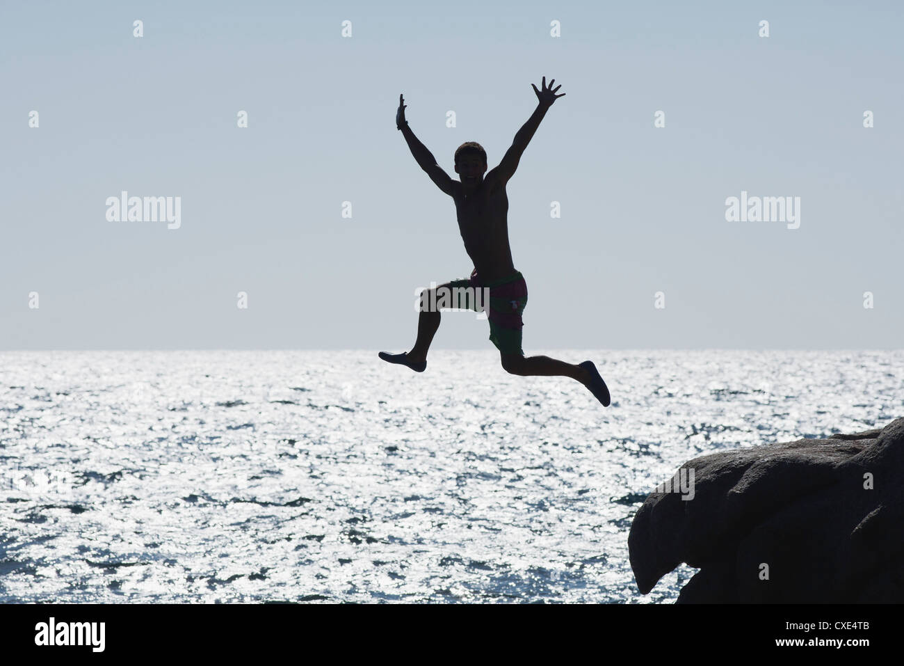 Teenage boy jumping into ocean, silhouette - Stock Image