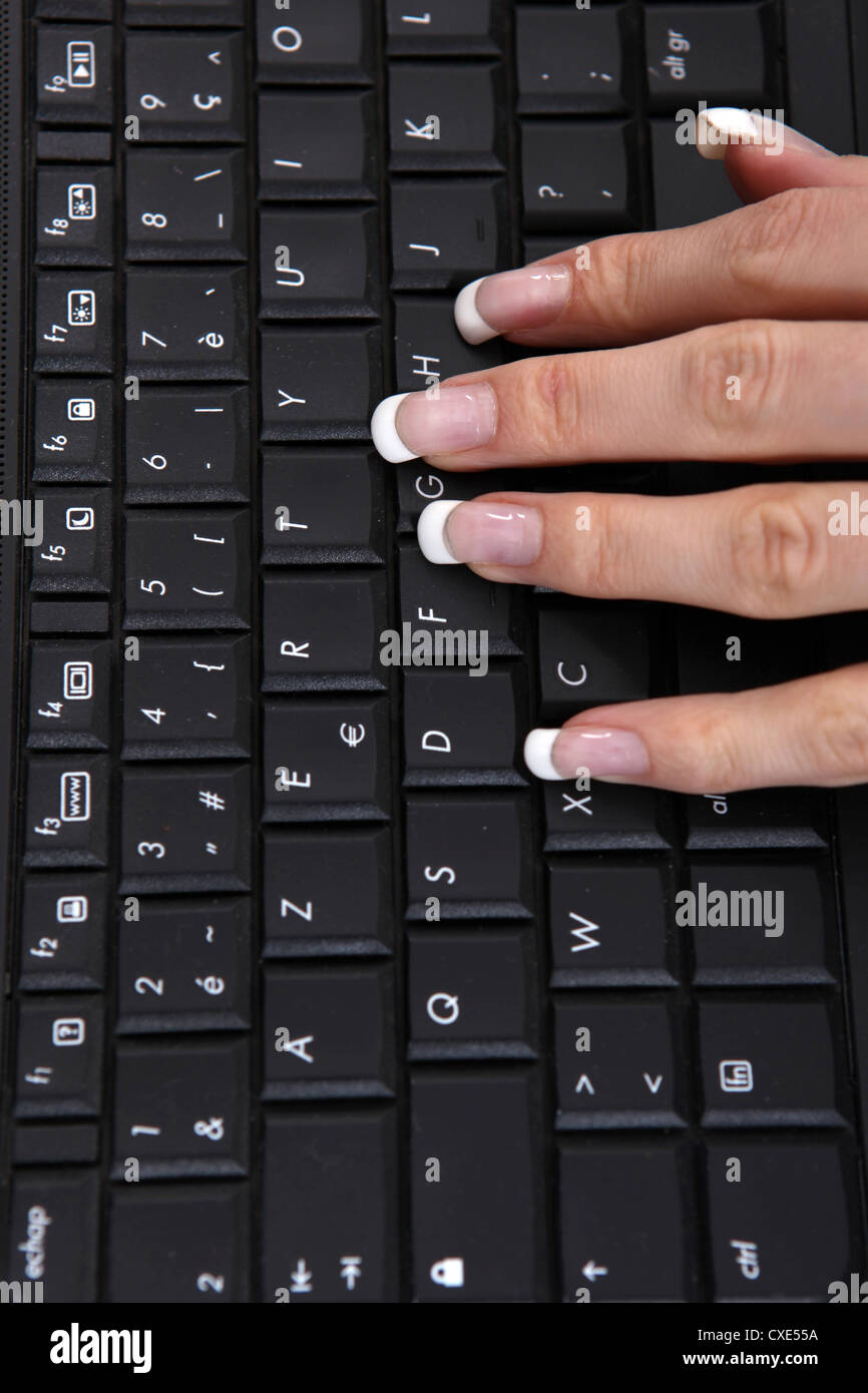 Manicured hand using a computer keyboard - Stock Image