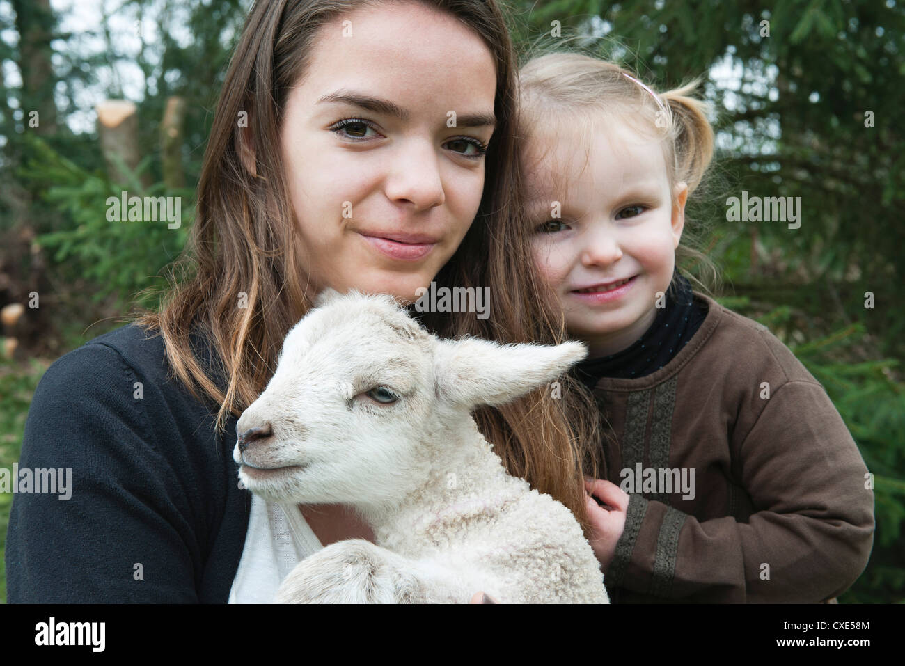 Teenage girl and little sister with pet lamb, portrait Stock Photo