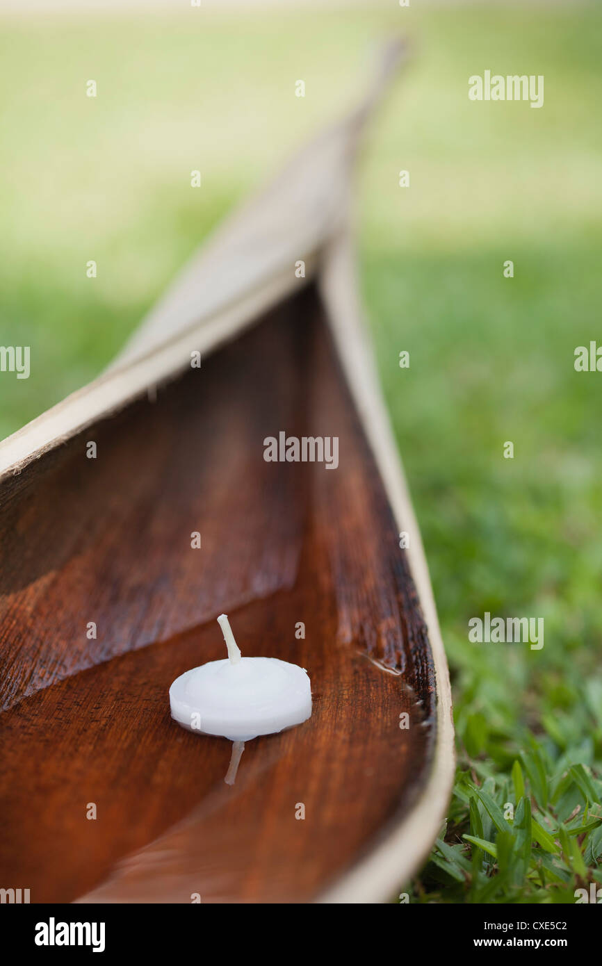Votive candle floating in water cupped within palm leaf - Stock Image