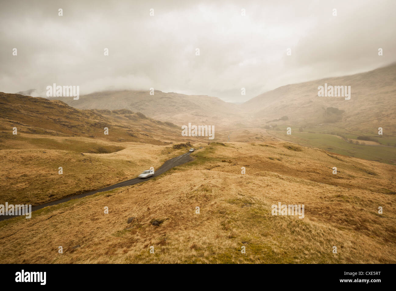 Looking down into Duddon Valley from the top of Hardknott Pass, cars ascending. Lake District National Park, Cumbria, - Stock Image