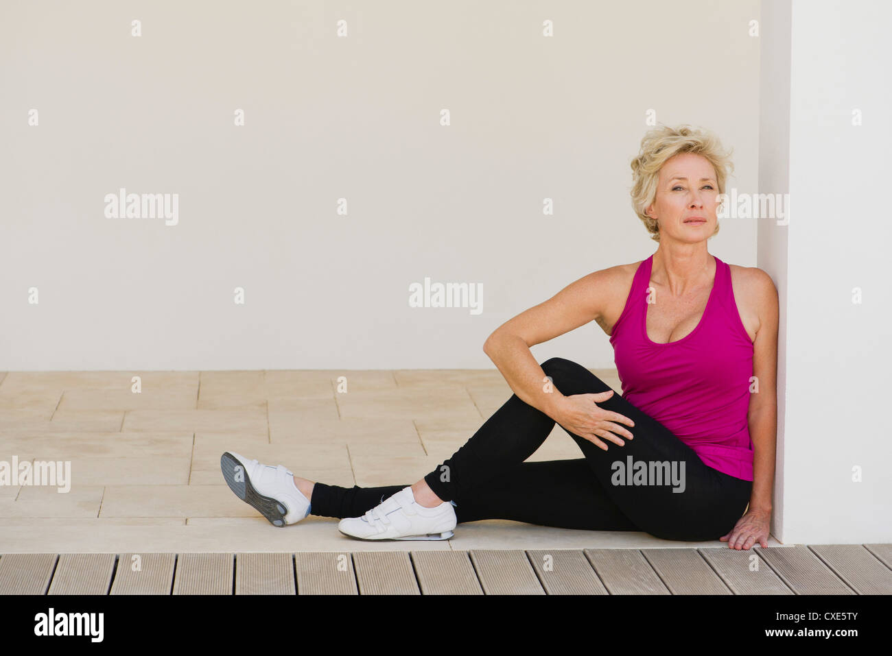 Mature woman doing spinal twist - Stock Image