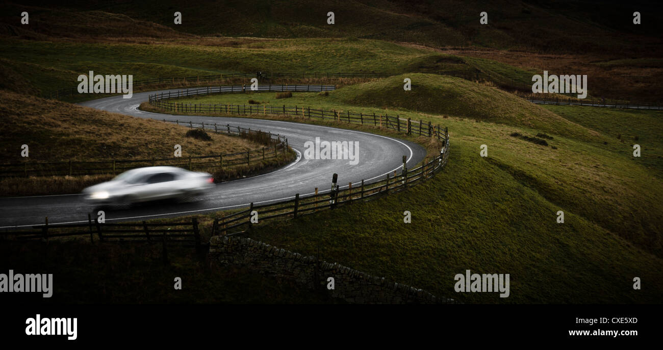 Silver sports car driving through winding road in Peak District National Park, Derbyshire, England, United Kingdom, - Stock Image