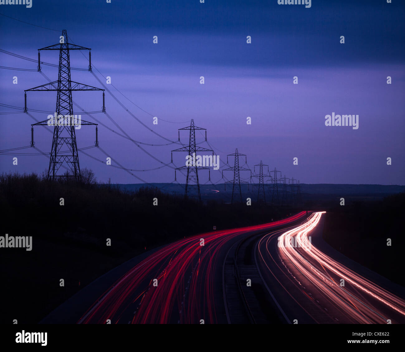 M40 Motorway light trails and power cables at dusk, Oxfordshire, England, United Kingdom, Europe - Stock Image