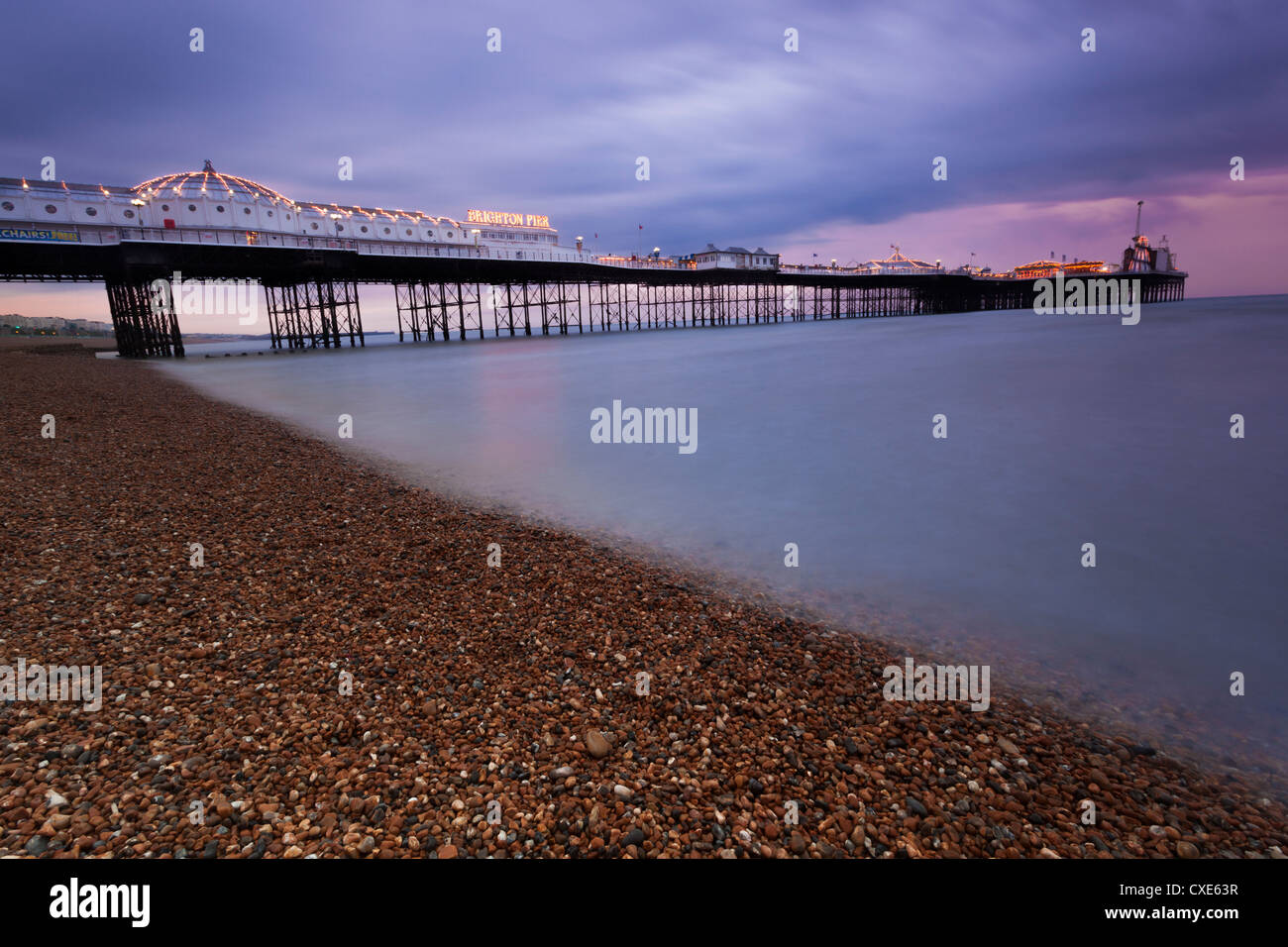 Looking out at Brighton Pier from Brighton beach, taken at sunset, Brighton, Sussex, England, United Kingdom, Europe - Stock Image