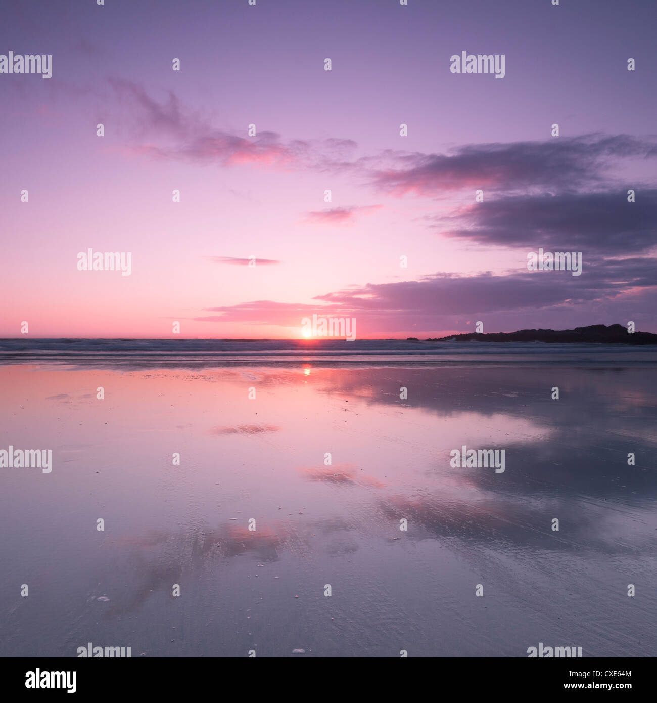 Sunset reflected in wet sand and sea on Crackington Haven Beach, Cornwall, England, United Kingdom, Europe - Stock Image